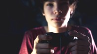 young teenager in dark bedroom playing console video game at night