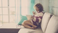 beautiful caucasian middle age woman with curly hair working at home and relaxing on the sofa with a tablet and internet. drinking tea or lemonade. happy relaxed leisure activity indoor