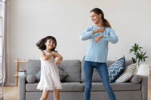 Mother and daughter dancing together in living room