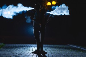 The man and woman smoke an electrical cigarette on the dark street. night time