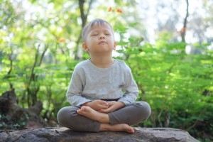 Cute little Asian 2 - 3 years old toddler baby boy child with eyes closed, barefoot practices yoga & meditating outdoors