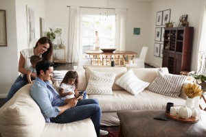 Young Hispanic family sitting on sofa reading a book together in their living room