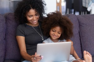 Smiling african mother and kid daughter having fun with computer