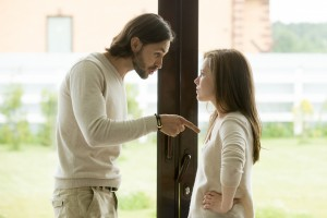Young couple arguing at home, man pointing finger blaming woman