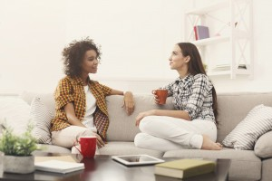 Two young female friends with coffee conversing