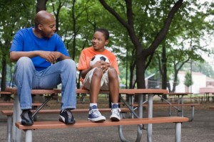 Man and boy sitting on picnic table with soccer ball