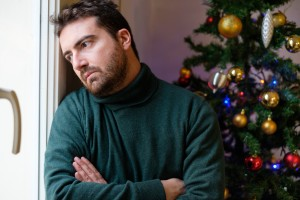 Sad man feeling negative emotions  and alone during christmas celebrations